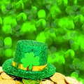 St patricks day hat and gold coins with green shamrock background Stock Images