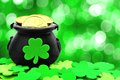St patricks day pot of gold and shamrocks over a green background Stock Photography