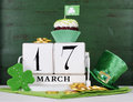 St patricks day save the date white vintage wood calendar happy with cupcakes on style green background Stock Photo