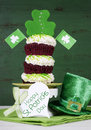 St patricks day shamrock green triple cupcake with greeting tag happy layer decorations and leprechaun hat against a vintage style Royalty Free Stock Photography