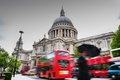 St paul s cathedral in london the uk red buses motion and man walking with umbrella Royalty Free Stock Image