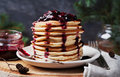 Stack of american pancakes or fritters with strawberry and blueberry jam in white plate on wooden rustic table decorated Christmas Royalty Free Stock Photo