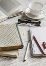 A stack of books, notebook and glasses , coffee cup on white wooden table. Royalty Free Stock Photo