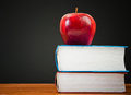 Stack of books with red apple and clean blackboard Royalty Free Stock Images