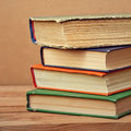 Stack of books vintage old on wooden deck table and grunge background Stock Photo