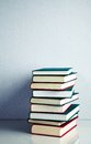 Stack of books on white reflective surface red green and black Royalty Free Stock Images