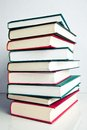 Stack of books on white reflective surface red green and black Stock Photos