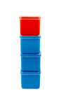 Stack of boxes one red on the top three blue in white with clipping path Royalty Free Stock Images