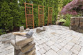 Stack of brick pavers for hardscape in backyard landscaping with trellis and trees Royalty Free Stock Image