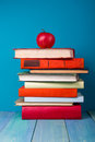 Stack of colorful books, grungy blue background, free copy space Royalty Free Stock Photo