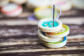 Stack of colorful buttons with sewing needle on a wooden table focus on the s eye very shallow depth field Royalty Free Stock Photography