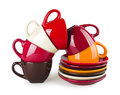 Stack of colorful mugs and saucers on white background Royalty Free Stock Photography