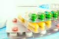 Stack colorful pills syringe medical table cutout composition selective focus Royalty Free Stock Images