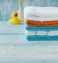 Stack of colorful towels and bath duck on the table Royalty Free Stock Photo