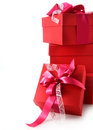 Stack of colourful red christmas gifts tied with pretty ribbons and bows on a white background with copyspace for your Royalty Free Stock Photos