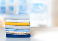 Stack cotton folded clothes on table indoors empty space. Royalty Free Stock Photo
