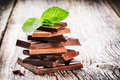 Stack of dark and milk chocolate pieces with mint leaf Royalty Free Stock Photo
