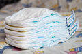 Stack of diapers on a baby s bd Royalty Free Stock Image