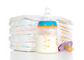 Stack of diapers nipple soother and baby feeding bottle with mil new born child milk on a white background Stock Photo