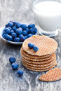 Stack of Dutch caramel waffles with blueberry and cup of milk Royalty Free Stock Photo