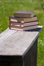 Stack of four hardcover books on old wooden bench Royalty Free Stock Image