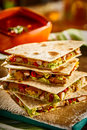 Stack of four quesadillas close up view on delicious wheat tortilla filled with meat avocado peppers and cheese with salsa bowl Royalty Free Stock Images