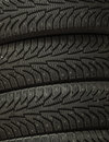 Stack of four wheel new black tires for winter car driving background macro closeup Royalty Free Stock Photo