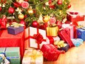 Stack of gift box by Christmas tree. Royalty Free Stock Photo