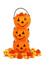 Stack of halloween jack o lantern candy holders over white with pile pumpkins and corn Stock Image