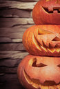 Stack of halloween jack o lanterns in vertical orientation on blurred stone background Royalty Free Stock Photo