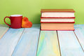 Stack of hardback books, diary on wooden deck table and green background. Back to school. Copy Space. Education