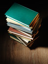 Stack of hardcover books arranged haphazardly viewed from a high angle on a wooden desk or table with copyspace and shadow behind Stock Photos