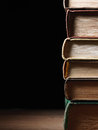 Stack of hardcover books arranged haphazardly viewed from a high angle on a wooden desk or table with copyspace and shadow behind Royalty Free Stock Photos