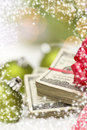 Stack of hundred dollar bills with bow near christmas ornaments one red green on snow flakes snow flake border Stock Images