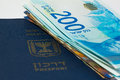 Stack of israeli money bills of 200 shekel and israeli passport Royalty Free Stock Photo
