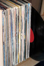 Stack of many vinyl records in old color covers on wooden shelf side view