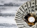 Stack of money dollars laid out like a fan with antique gold watch Royalty Free Stock Photo