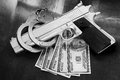 Stack of money gun and handcuffs on table Stock Photo