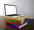 Stack multi colored books laptop top electronic education concept Stock Images