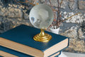 Stack of old books, branches in vase, glass globe, grunge brick Royalty Free Stock Photo