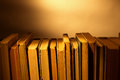 Stack of old hardcover books on a wooden surface against a row Royalty Free Stock Images
