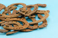 Stack of old retro horse shoes on blue Stock Photo