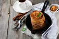 Stack of pancakes from buckwheat flour with baked apples and cinnamon on old wooden background. A healthy breakfast. Royalty Free Stock Photo
