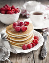 Stack of pancakes with fresh raspberries.