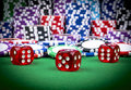 Stack of Poker chips on a green gaming poker table with poker dice at the casino . Playing a game with dice. Casino dice Concept Royalty Free Stock Photo