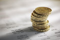 Stack of pound coins on financial figures balance sheet Royalty Free Stock Photo