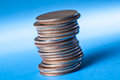 Stack of quarters uneven with dramatic lighting on blue background Royalty Free Stock Photography