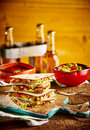 Stack of quesadillas with guacamole bowl four quesadilla wedges on wooden cutting board next to and beer bottles in background Royalty Free Stock Images