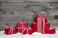 Stack of red christmas gifts snow on grey wooden background as a voucher with giftboxes for with Royalty Free Stock Photo
