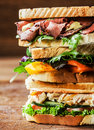 Stack of three delicious toasted sandwiches with different fillings including rare roast beef shredded chicken breast and pepper Stock Photography